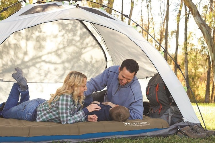 Father, mother and their child inside a white camping tent