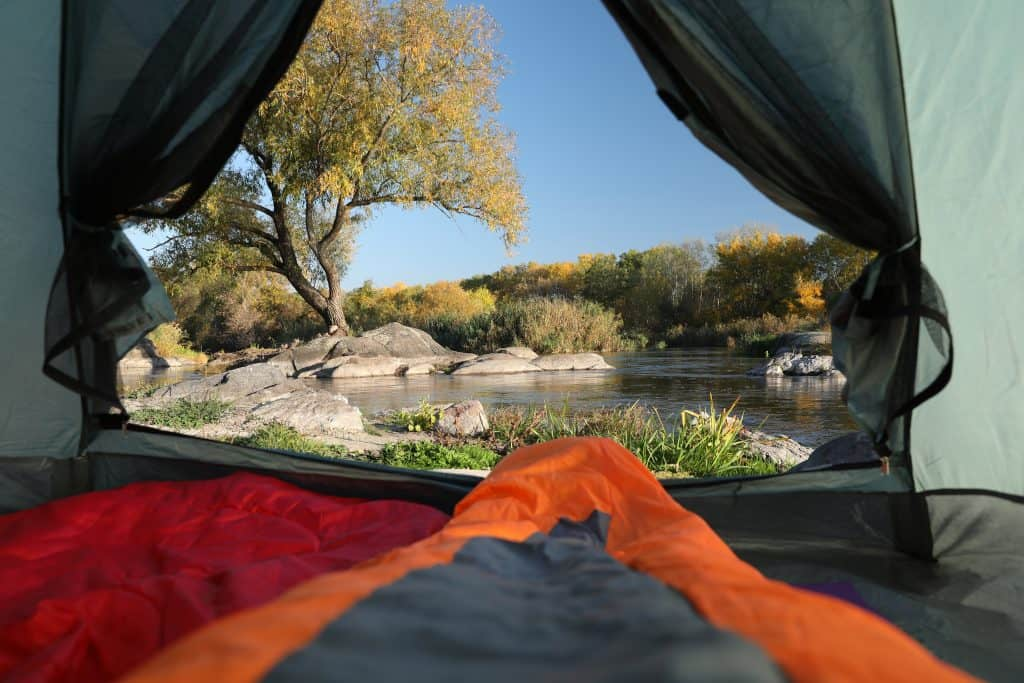 camping mattress inside a camp tent with lake view