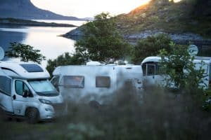 white camping cars parked beside lake
