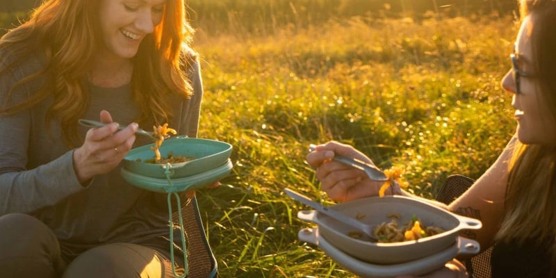 two girls eating on grass with mess kit