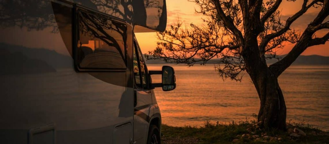 sunset in a lake with trees and white camping car